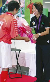 母校弥栄高の後輩から花束を贈られる岩清水選手(右)