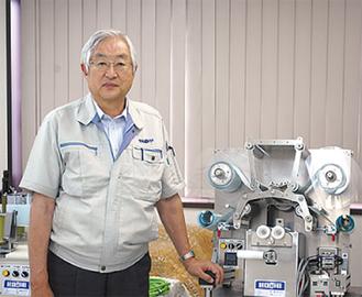 自慢の製品と並ぶ田中社長