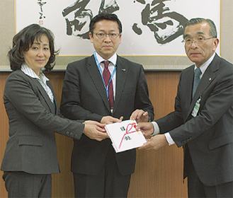 寄付をする山重校長(左)と細谷実行委員長(中央)