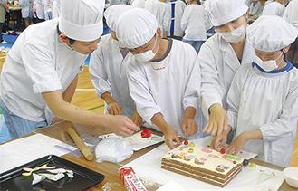 セ・ラ・セゾンスタッフの指導の下、完成に向けてカラフルなケーキを前に真剣な目で取り組む児童ら=21日、淵野辺東小