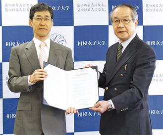 協定書を手にする風間学長(左)と宮崎理事長
