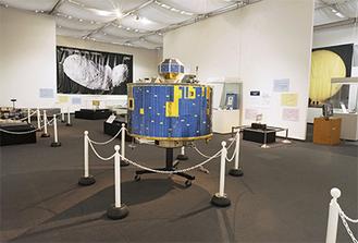 奥に見えるのが「はやぶさ」が撮影した小惑星イトカワの姿。手前の探査機は「ひてん(飛天)」(1990年打ち上げ、実物大模型)。のちの「はやぶさ」の旅にも欠かせない「スイングバイ」という技術を日本が習得するのに貢献した