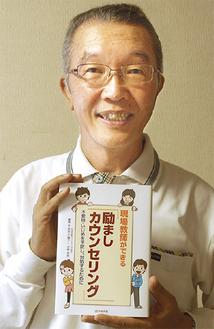一部を執筆した新書を持つ講師の山上隆男さん