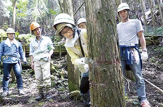 間伐作業を行う社員とその家族ら