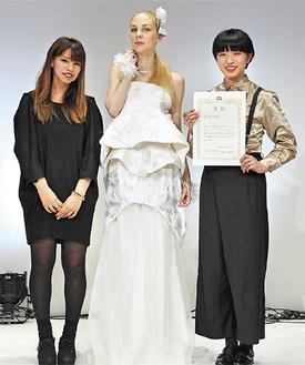 デザインしたドレスと並ぶ秋森さん(右)、上江洲さんの区内出身ペア
