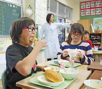 特別給食で振る舞われた「きなこあげパン」を頬張る児童