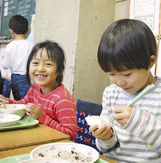 笑顔を浮かべて美味しそうに食べる清新小の児童