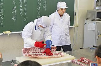 豚枝肉を解体する中村氏(左)と楠木社長