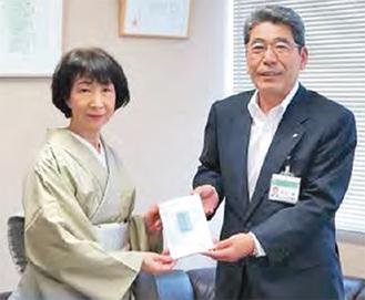 本を寄贈する中澤さん(左)