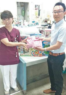 玩具などを寄贈する高木代表理事(右)