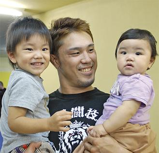 練習の合間に長男の勇斗君と長女の美織ちゃんを抱える粕谷選手(上)=1日、総合格闘技道場CROWN