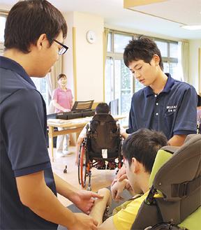 利用者に語りかける市成君(左)と喜田君(右)=15日、ワゲン療育病院長竹