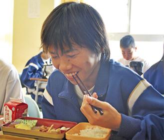 笑顔で特別給食を頬張る由野台中の生徒=18日