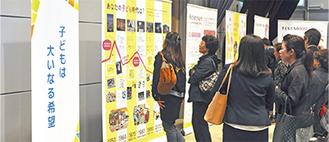 少子高齢社会をテーマとしたパネルを見学する来場者=11月22日、市立産業会館