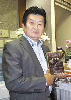 受賞の盾を手にする久野社長