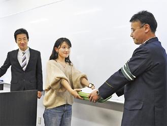 佐久間交通第一課長からアンケートを受け取る滝口さん(中央)と坂田教授=18日、桜美林大学