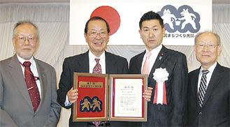 赤間二郎総務副大臣から表彰を受ける堀口会長(中央左)ら