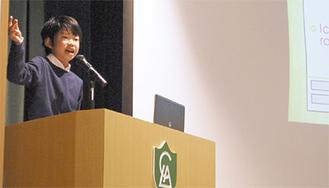 (上)身振りを交えながら大人顔負けのスピーチをした平田くん=10日、LCA国際小学校