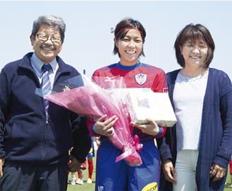 花束を手に笑顔の長澤選手