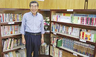 手作りの本棚に並べられた図書と並ぶ金ヶ江会長