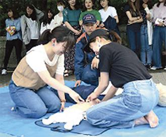 消防士に指導を受ける学生