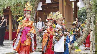 華やかな衣装をまとい、茅の輪をくぐる子どもたち=25日、亀ヶ池八幡宮