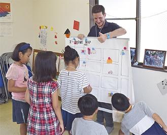 地域の子どもたちに英会話を教えるベルワードさん=22日、横山2丁目自治会館