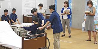 設定で右手足を麻痺した女性を介助する津久井高生徒(中央)