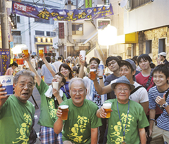 ビールを手に乾杯する実行委員と若者ら