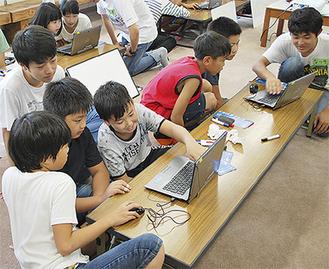 サレジオ工業高等専門学校の生徒らのサポートのもとプログラミング体験をする子どもたち=23日、中央小