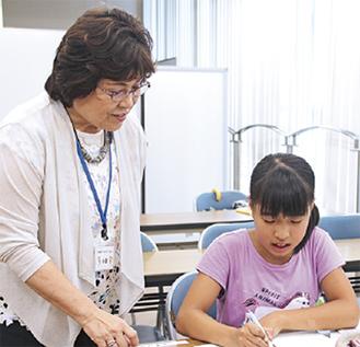 児童に助言する小田さん(左)=25日