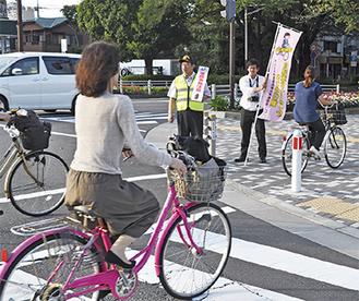 自転車通行者に注意を呼びかける会員ら=21日、相模原警察署前交差点