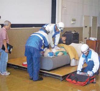 消防職員などの指導のもと訓練を行う参加者