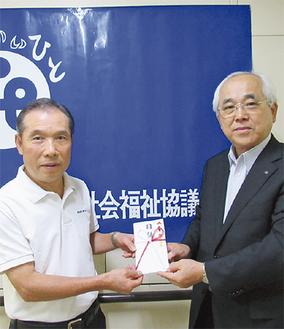 目録を手渡す大沼社長(左)