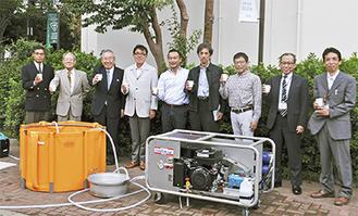 防火水槽と造水機で生成した飲料水を手にする関係者ら=9月27日