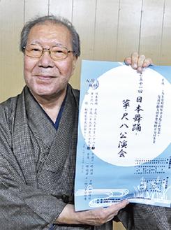 ポスターを手にする坂東会長