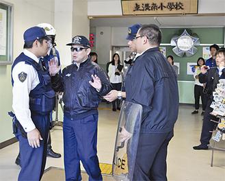 教職員から駆け付けた警察官に引き渡される不審者役