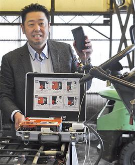 フォークリフトのバッテリーにインバーターを繋ぎ携帯電話を充電する横江社長