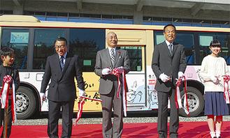 ラッピングされたバスを背に出発式でテープカットする加山市長ら