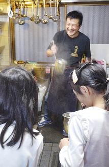 笑顔で湯切りを教える浅沼さん=市社会福祉協議会提供