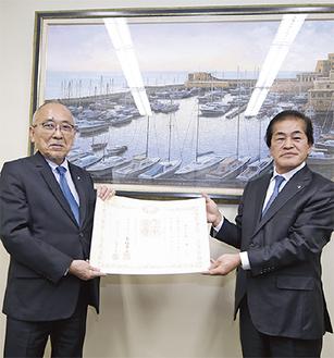 伝達式での祇園会長(左)と梅沢副市長=(株)ギオン本社