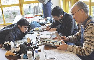 お気に入りのおもちゃを修理する様子を心配そうに見守る男の子=富士見こどもセンター