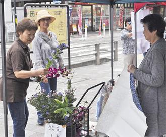 野菜とともに店頭に並ぶ花などを買い求める人々
