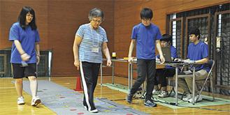 北里大学介護予防チームのもと、認知機能の診断を兼ねた歩行測定を行う参加者(昨年8月)
