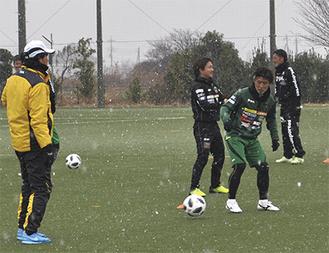 雪が舞う中、練習を見守る西ヶ谷新監督(左)と選手ら