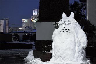 通りかかる人の人気者となった雪だるま=23日、中央1丁目
