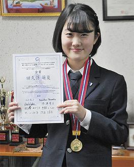 金賞のメダルと表彰状を手に笑顔の田久保さん