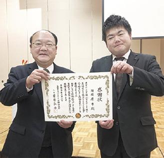 感謝状を手にする市川会長(右)