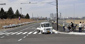 開通した東西道路を通る車両=26日正午過ぎ撮影