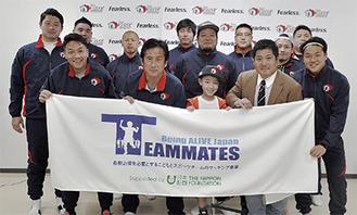 ライズの「大男」たちに温かく囲まれ、笑顔を見せる剛道君(中央右)=18日、ノジマフットボールパーク